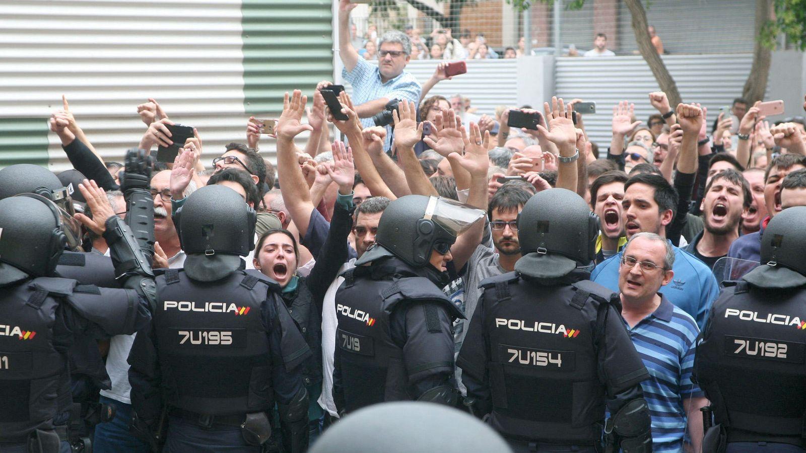 Foto: Agentes de la Policía Nacional forman un cordón policial en el exterior del IES Tarragona el pasado 1 de octubre. (EFE)