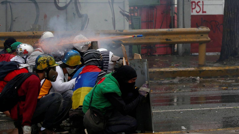 Manifestantes se enfrentan a las fuerzas de seguridad durante una marcha opositora, en Caracas. (Reuters)