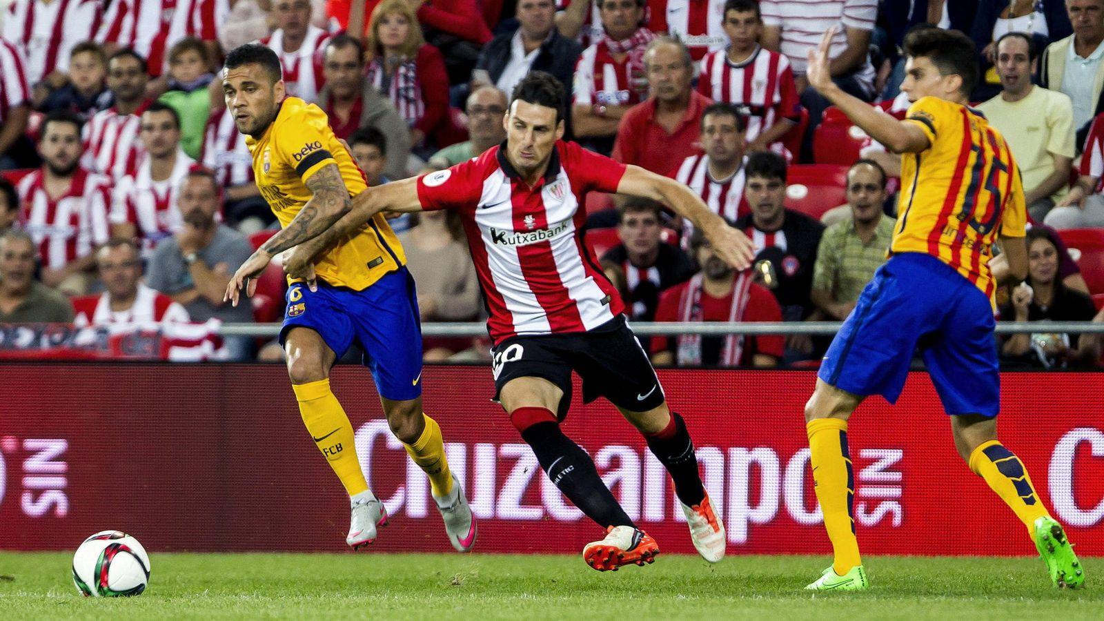 Foto: Aduriz, entre Dani Alves y Bartra, durante el partido de ida de la Supercopa de España (EFE)