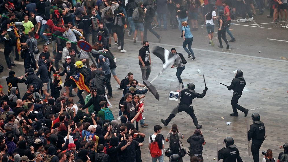 Foto: Los Mossos d'Esquadra cargan contra los miles de personas que se agolpan ante el aeropuerto de El Prat. (EFE)