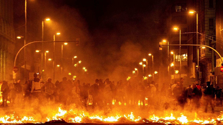Los manifestantes incendian cartones junto a la Delegación del Gobierno en Barcelona. (EFE)