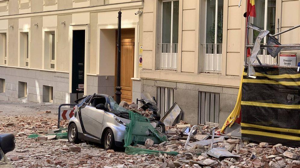 Foto: Un vehículo estacionado frente al inmueble ha resultado dañado por la caída de la cornisa. (Emergencias Madrid)