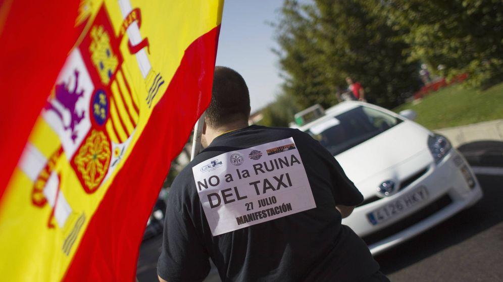Foto: Un taxista sostiene una bandera de España durante una manifestación del sector en Madrid. (Foto: Reuters)