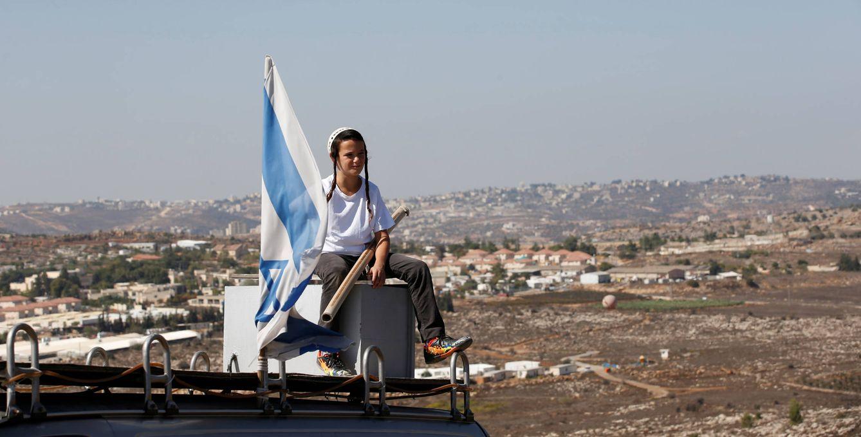 Foto: Un niño israelí junto a una bandera en la entrada de la colonia de Amona, en Cisjordania, durante una protesta contra su desmantelamiento, el 20 de octubre de 2016 (Reuters).