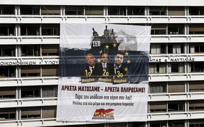 Foto: Un enorme cartel critica al ex primer ministro Samarás y a Tsipras en la sede del Ministerio de Finanzas. (Reuters)