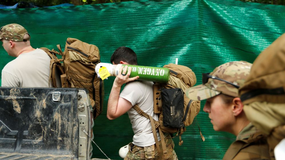 Foto: Militares estadounidenses cargan cilindros de oxígenos hacia la gruta Tham Luang. (Reuters)