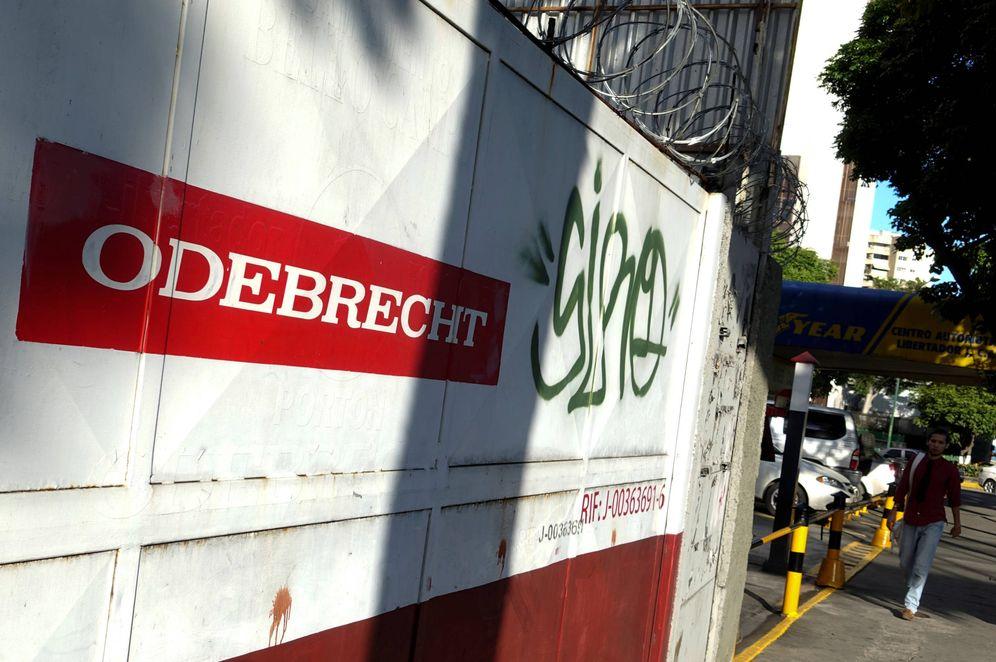 Foto: Un hombre pasa ante unas obras con el logo de Odebrecht, en Caracas, Venezuela. (Reuters)