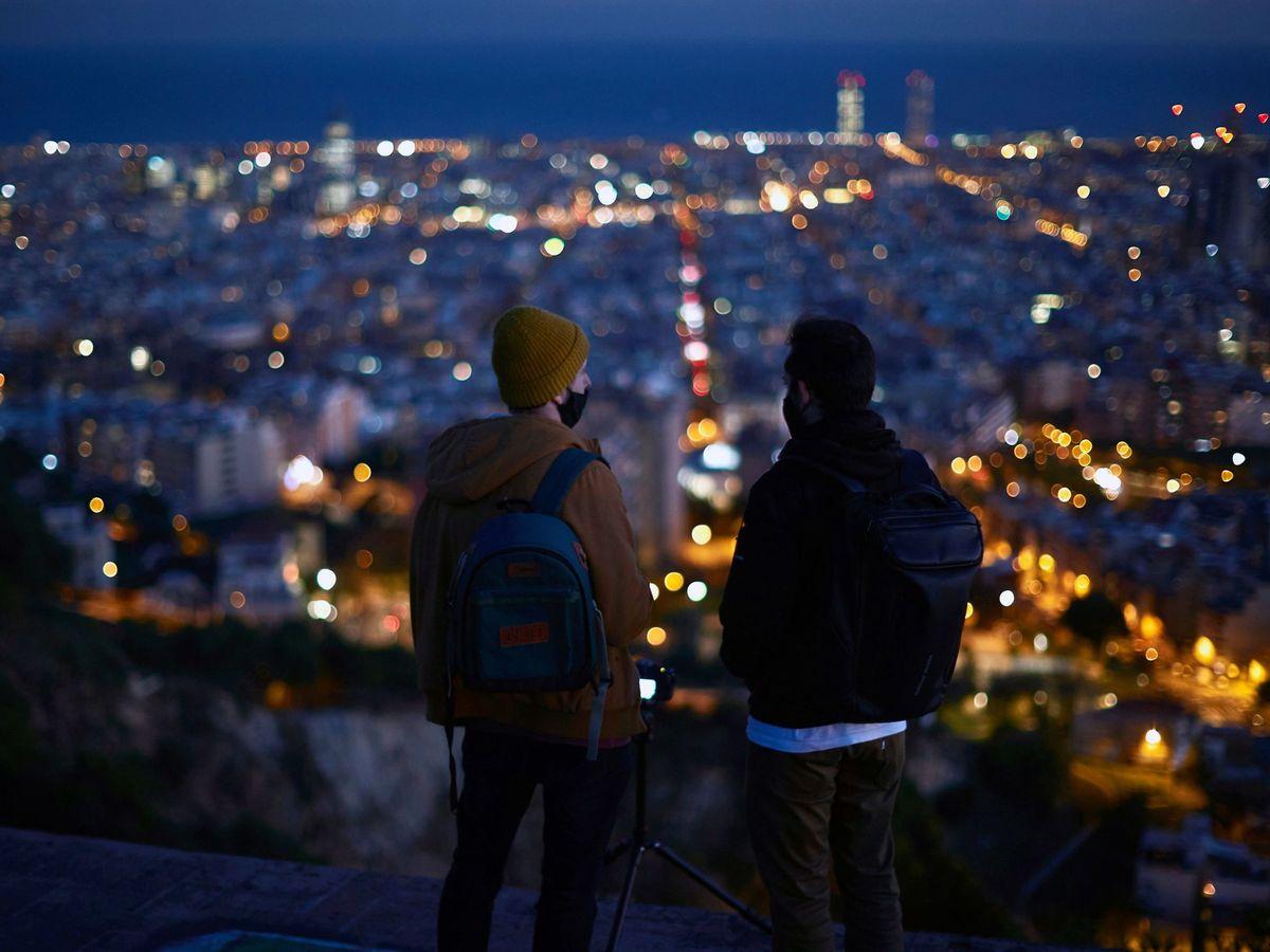 Foto: Dos personas observan el atardecer desde un mirador en Barcelona (EFE)