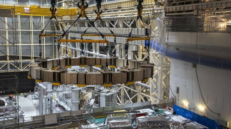 La quinta y última bobina de campo poloidal suspendida sobre el pozo del reactor