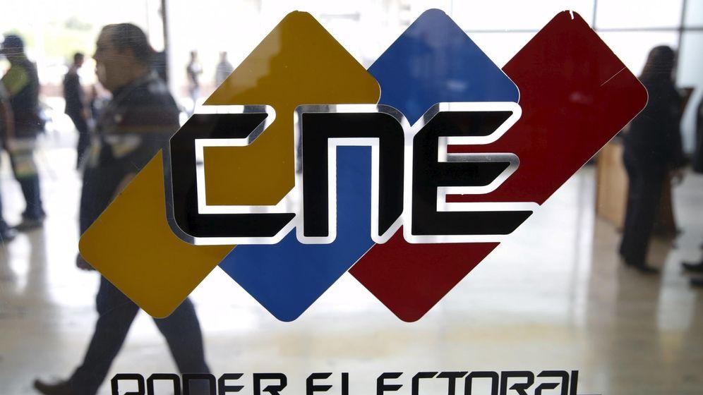 Foto: Venezolanos pasan ante un logo del Consejo Nacional Electoral, en su sede en Caracas, el 2 de diciembre de 2015 (Reuters).