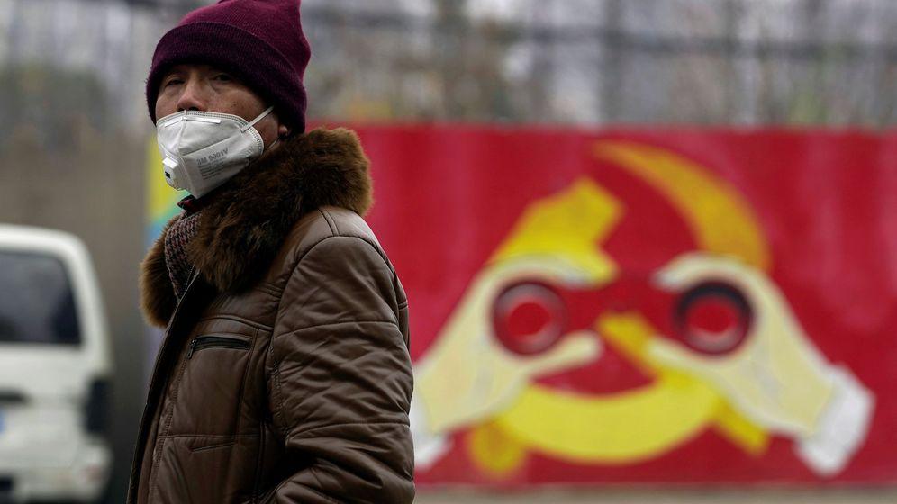 Foto: Un hombre porta una mascarilla frente a una imagen modificada del emblema del PCC. (Reuters)