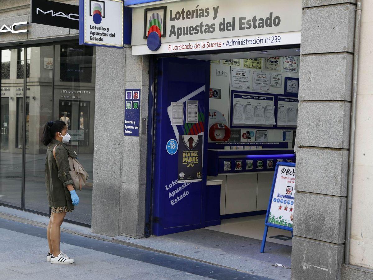 Foto: Foto de archivo de una mujer esperando para entrar en una administración de lotería de Madrid. (EFE)