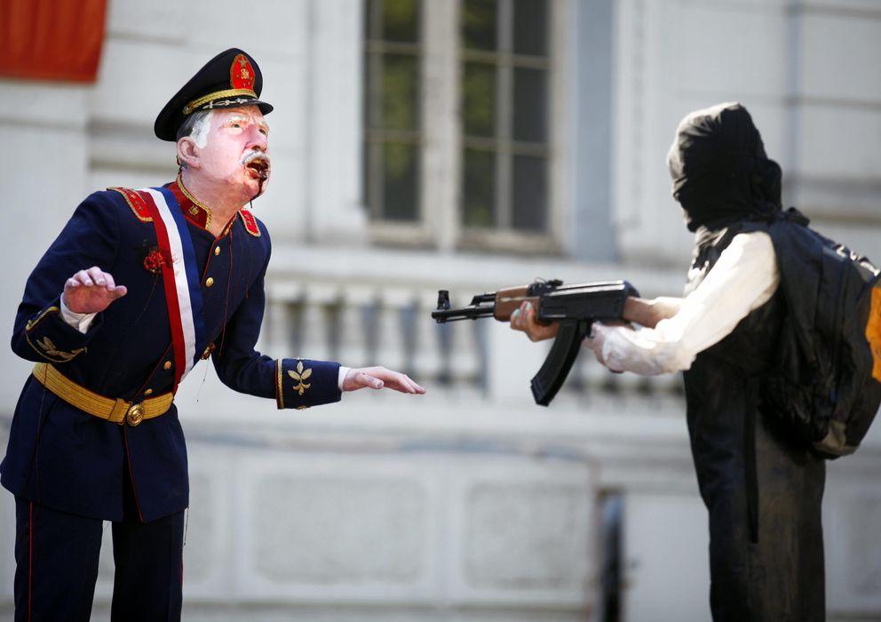 """Foto: El artista Francisco Pacheco """"acribilla"""" a Augusto Pinochet en pleno centro de Santiago de Chile. (EFE)"""
