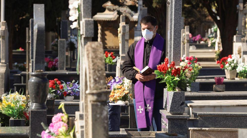 Foto: Un sacerdote hace un responso durante un entierro sin asistentes en el cementerio de Salamanca. (EFE)