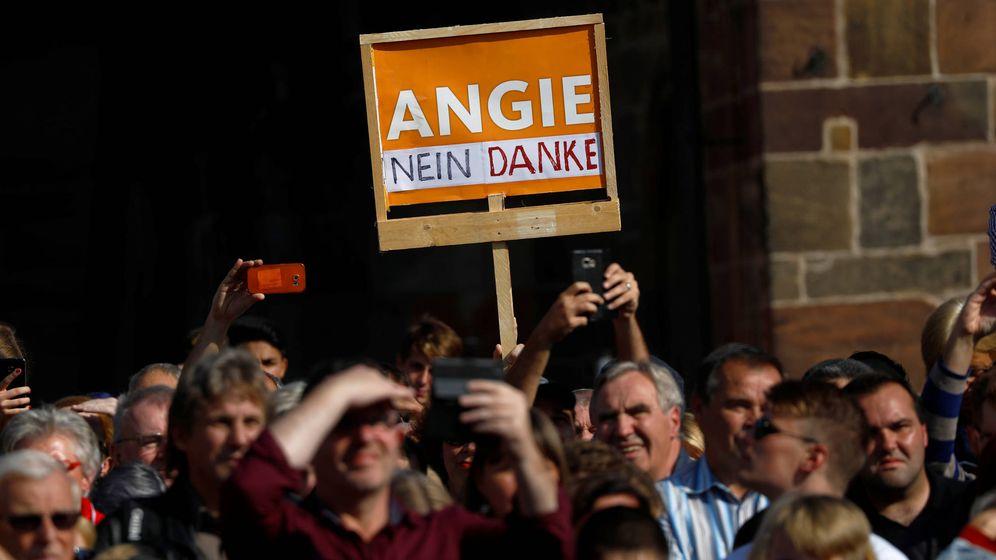 Foto: Manifestantes con una pancarta que reza Angie, no gracias, durante un mitin de la canciller en Fritzlar. (Reuters)