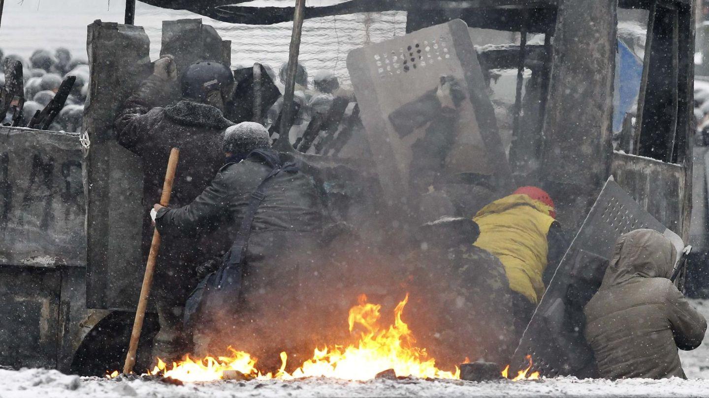 Manifestantes se protegen durante choques con la Policía (Reuters).