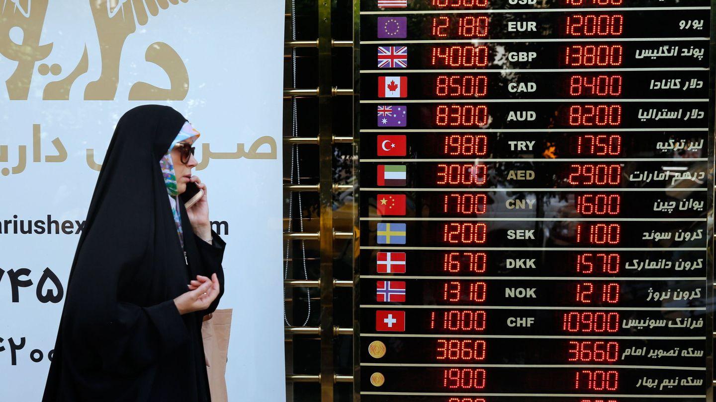 Una mujer iraní pasa por delante de una casa de cambio en Teherán en agosto de 2018, en pleno desplome del rial tras la reimposición de sanciones estadounidenses. (EFE)