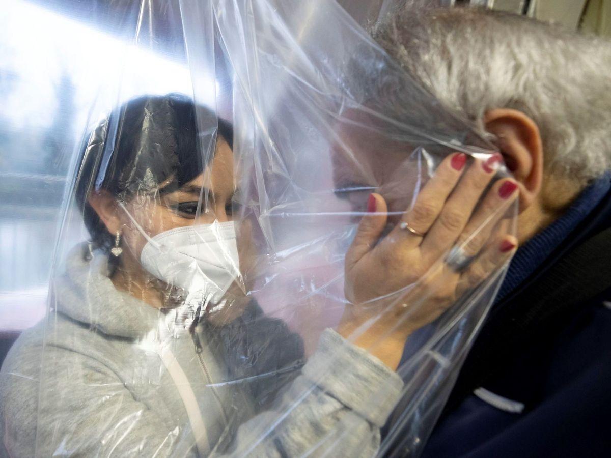 Foto: Una mujer con mascarilla acaricia a una anciana a través de una cortina especial en Roma. (EFE)