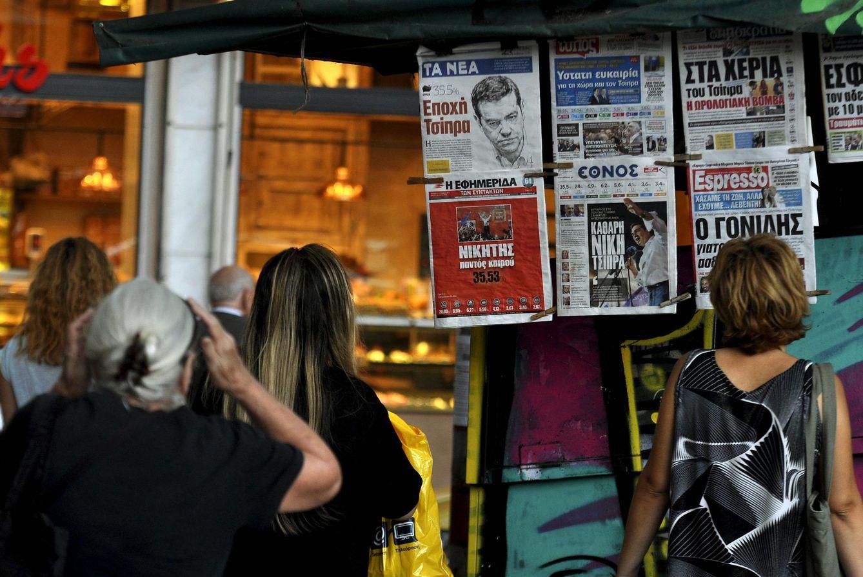 Foto: Griegos observan los periódicos con los resultados de las elecciones en sus portadas en un quiosco de Atenas, el 21 de septiembre de 2015 (Reuters).