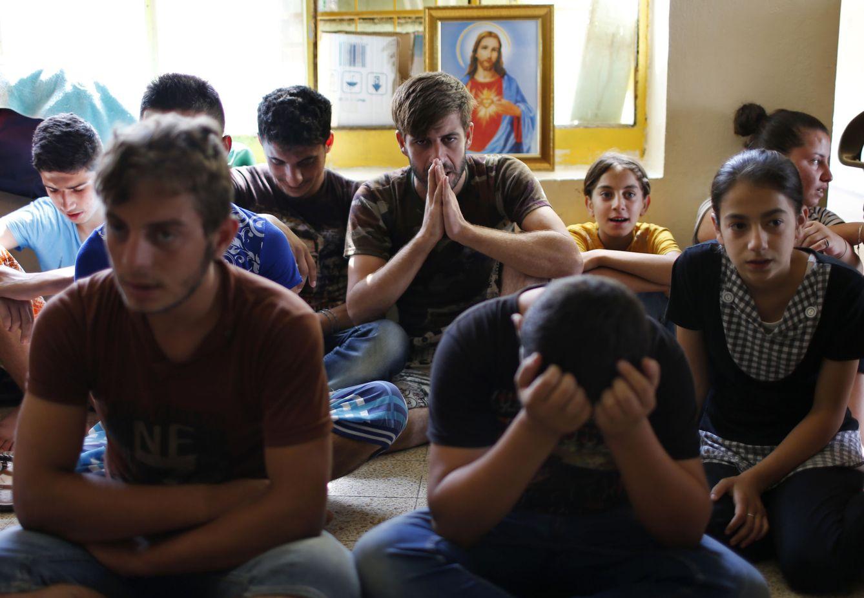 Foto: Cristianos iraquíes, desplazados por el avance del Estado Islámico, rezan en una escuela que ejerce de campo de refugiados en Erbil, en septiembre de 2014. (Reuters)