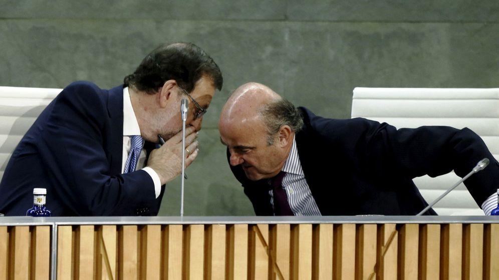 Foto: El presidente del Gobierno en funciones, Mariano Rajoy, conversa con el ministro de Economía en funciones, Luis de Guindos, en el acto de presentación del libro. (EFE)
