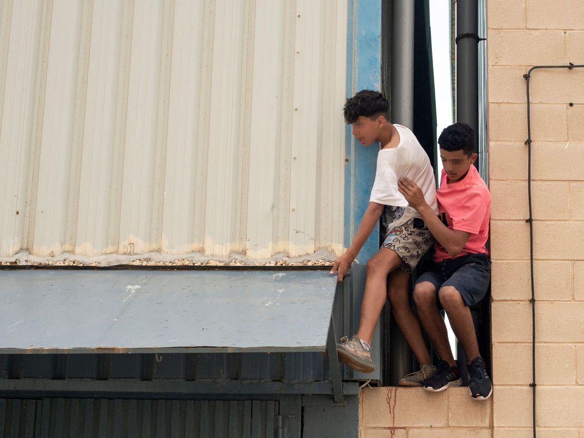 Foto: Dos migrantes se escapan de la nave del polígono industrial cercano a la playa de El Tarajal en mayo. (EFE)