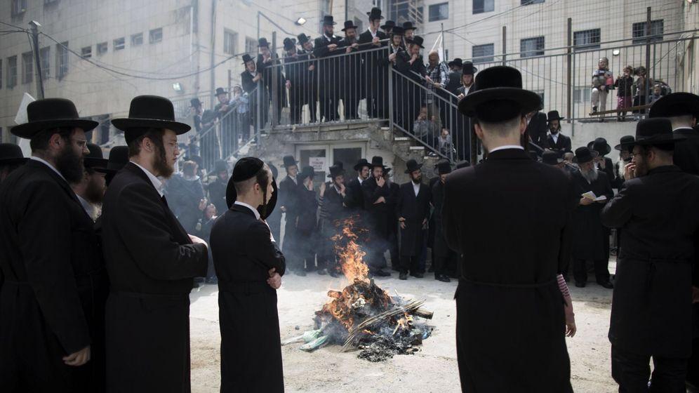 Foto: Varios judíos ultraortodoxos rezan mientras se procede a la quema de pan con levadura en el barrio de Mea Shearim en Jerusalén. (EFE)
