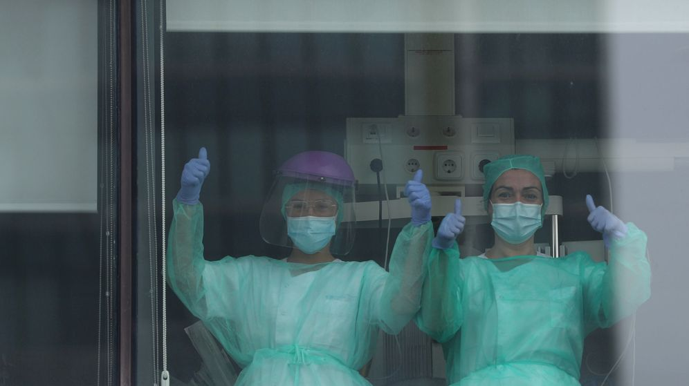 Foto: Dos enfermeras saludan desde las ventanas de La Paz, en Madrid. (Reuters)
