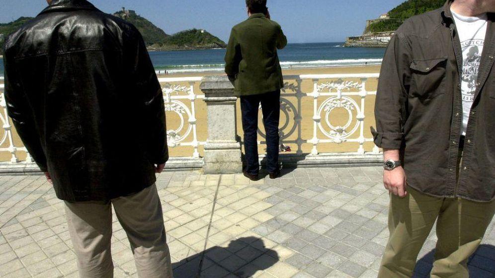 Foto: Un cargo público vasco (en el centro) es protegido por sus escoltas en el paseo de La Concha de San Sebastián en 2001. (EFE)