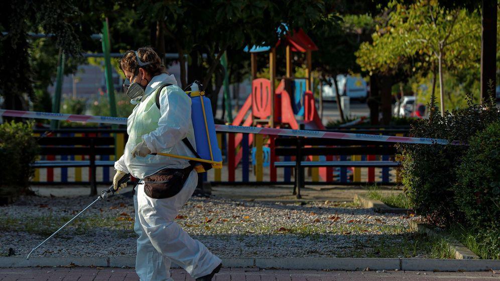Foto: Una trabajadora municipal desinfecta las proximidades un parque infantil clausurado. (EFE)
