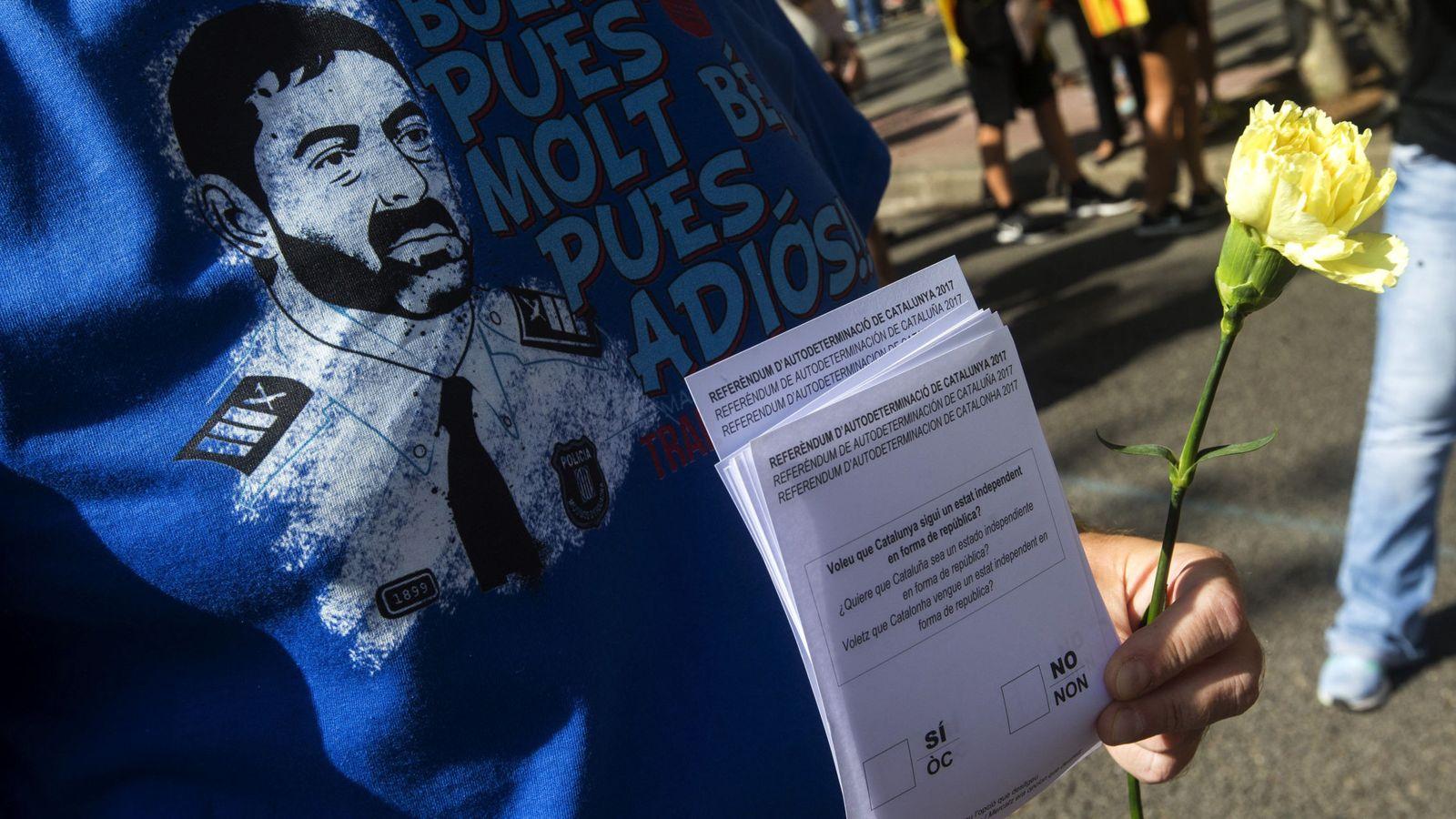 Foto: Una persona con la camiseta del 'major' de los Mossos, Josep Lluis Trapero, y papeletas del referéndum. (EFE)