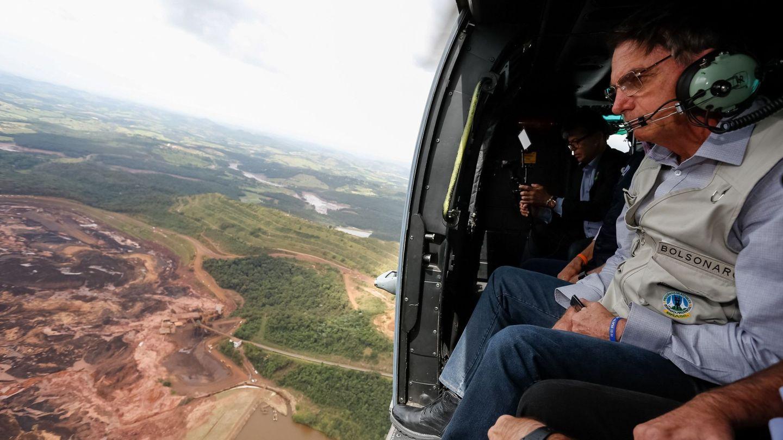 Fotografía cedida por la Presidencia de Brasil que muestra al presidente Jair Bolsonaro mientras sobrevuela la zona afectada por una avalancha en Brumadin. (EFE)