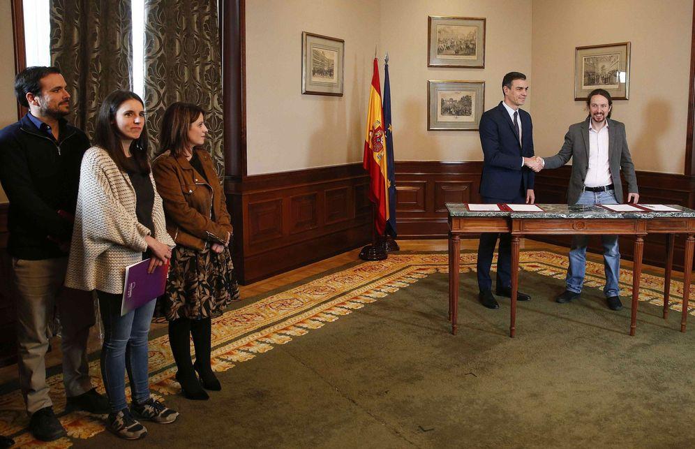 Foto: Pedro Sánchez y Pablo Iglesias firman el acuerdo ante la mirada de Adriana Lastra, Irene Montero y Alberto Garzón, este 12 de noviembre. (EFE)