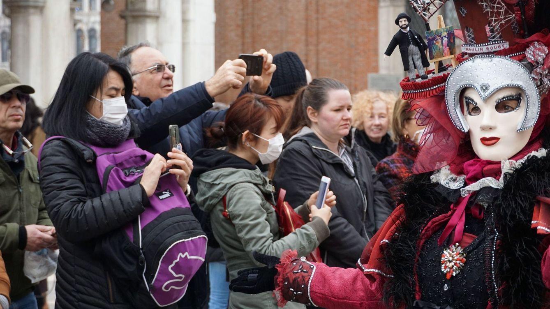 Foto: Turistas con máscaras protectoras visitan la Plaza de San Marcos, el lunes en Venecia (Italia). (EFE)