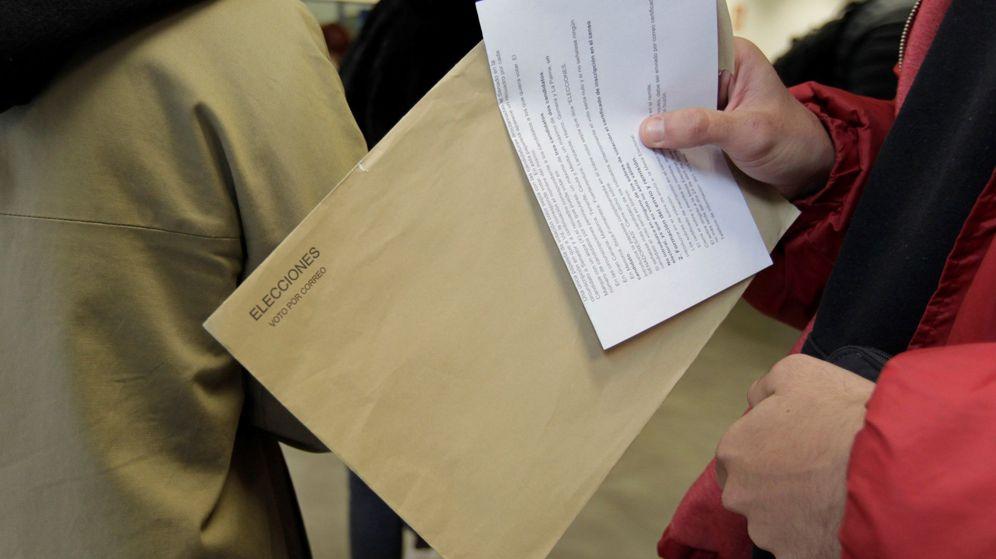 Foto: Un grupo de ciudadanos hace cola para votar por correo. (EFE)