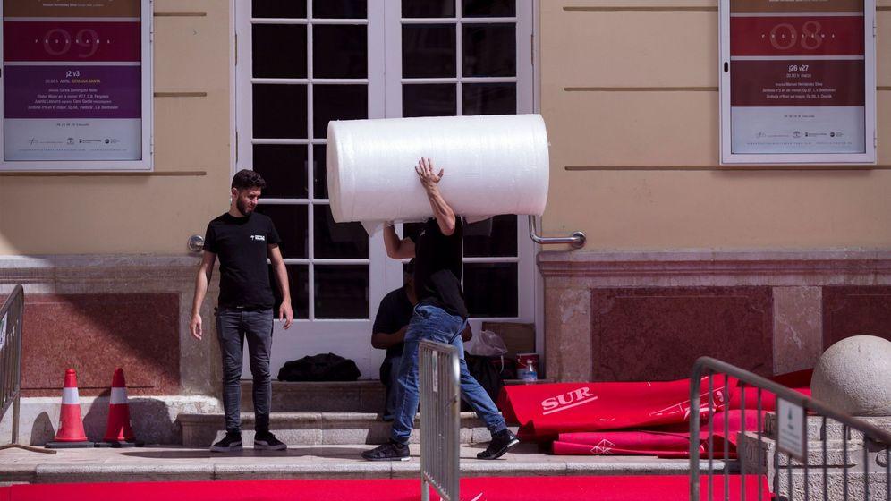 Foto: Técnicos recogen la alfombra roja del Festival de Málaga, aplazado la semana pasada por el coronavirus. (Efe)