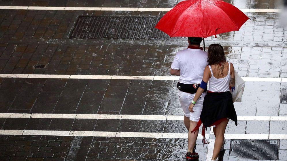 Foto: Dos personas se protegen de la lluvia en una de las céntricas calles de Pamplona, esta tarde durante la fiesta de San Fermín. (EFE)