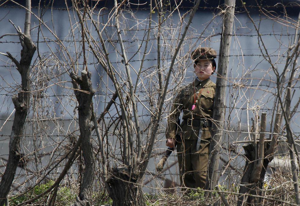 Foto: Una guardiana de prisiones norcoreana custodia la verja de una cárcel junto al río Yalu, en la frontera con China, en mayo de 2011. (Reuters)