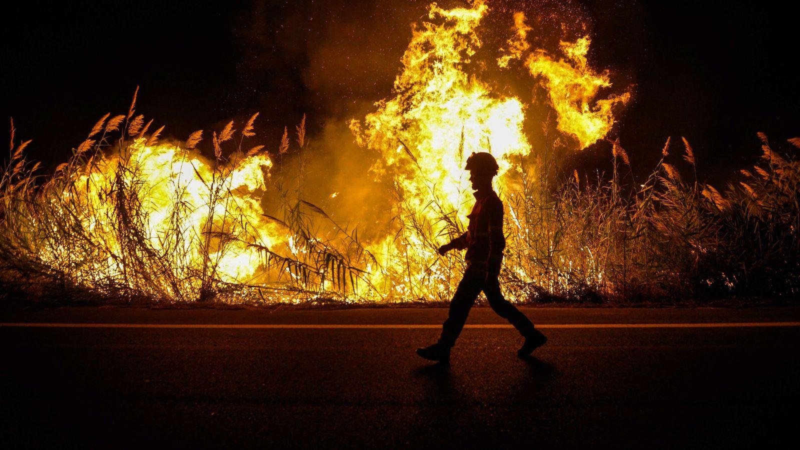 Foto: Un bombero camina junto a uno de los focos durante las tareas de extinción en Caldas da Rainha, Portugal. (EFE)