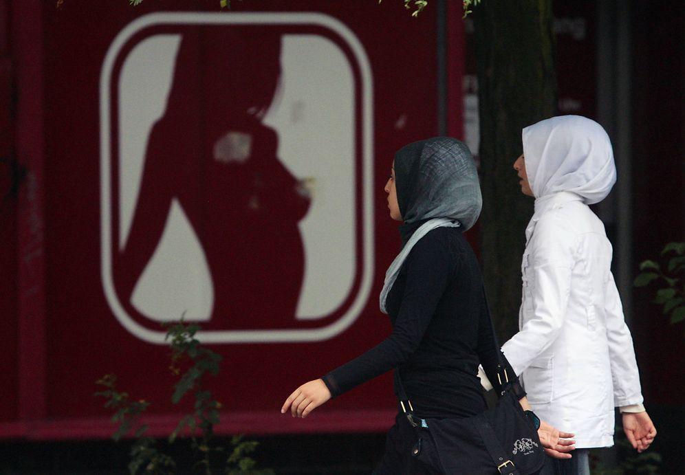 Foto: Dos chicas con velo pasan ante el cartel de un 'sex shop' en Berlín, en julio de 2017. (Reuters)