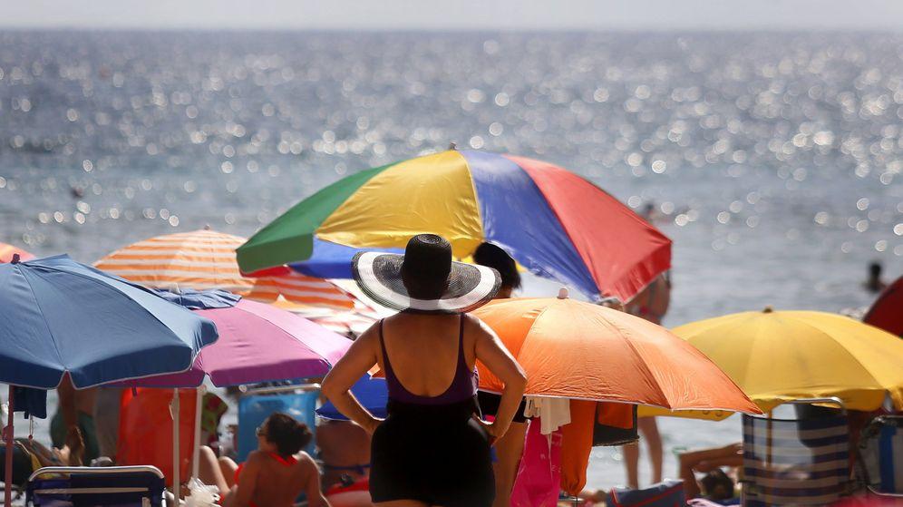 Foto: Varios turistas disfrutan del sol y el agua en la playa de Levante de Benidorm. (Efe)