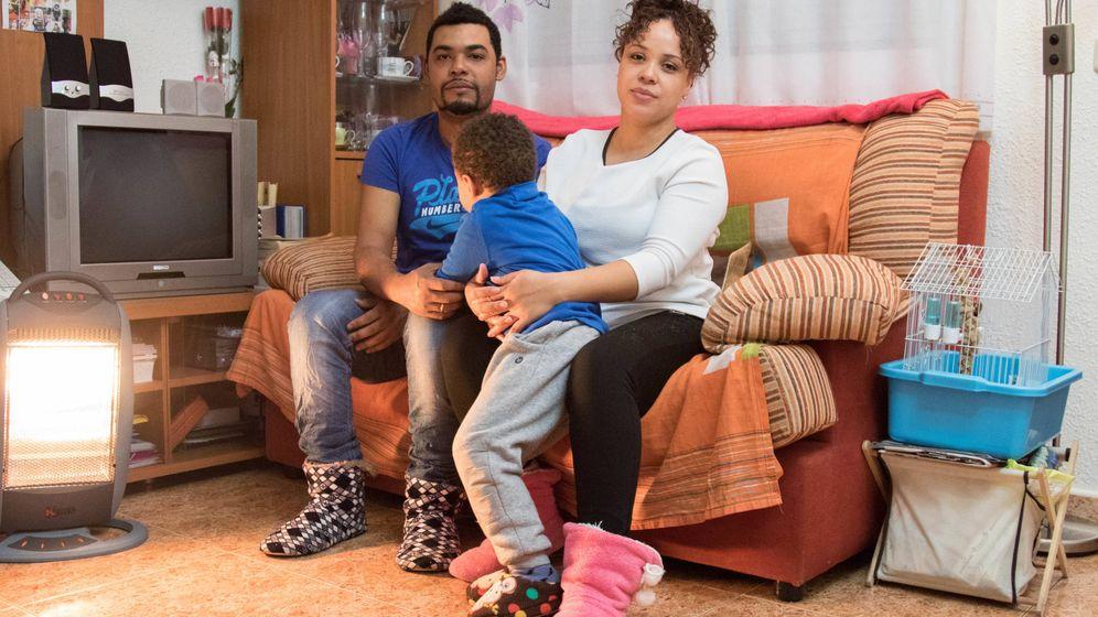Foto: Carlos y Carine posan junto a su hijo en su salón. Los dos trabajan pero no llegan a pagar el alquiler. (D. B.)