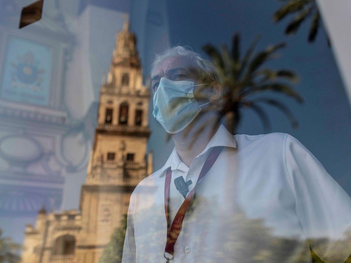 Foto: Un trabajador mira a través de una cristalera con la imagen reflejada de la Torre de la Mezquita-Catedral de Córdoba. (EFE)