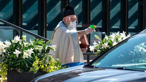 Un sacerdote usa una pistola de juguete para bendecir con agua bendita a fieles