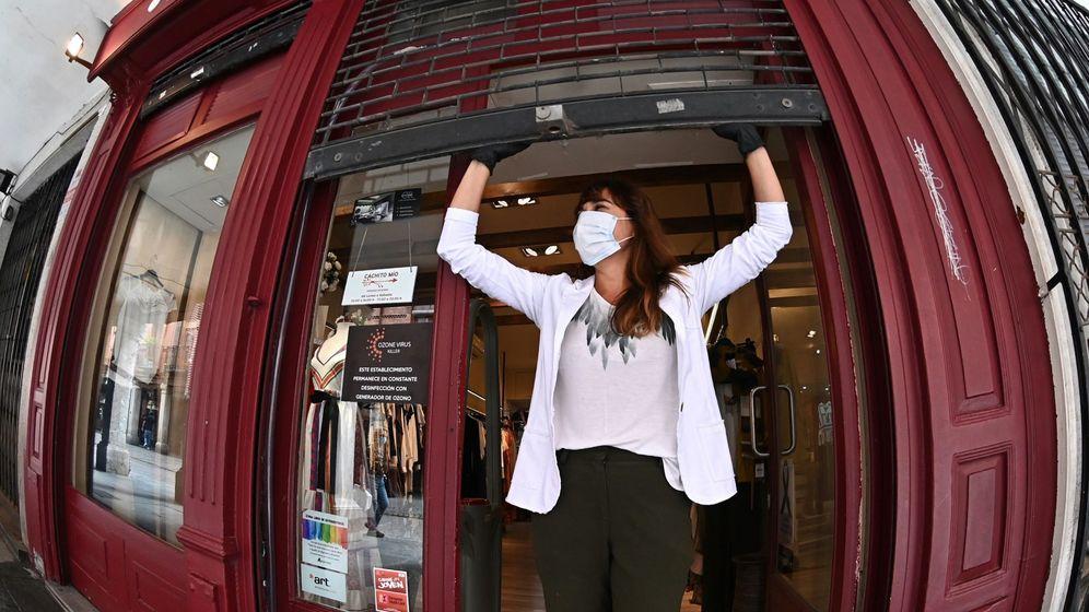 Foto: Una persona abre su comercio de ropa en Alcalá de Henares, con un cartel en el que informa de la desinfección constante mediante ozono del estableciemiento.(EFE)