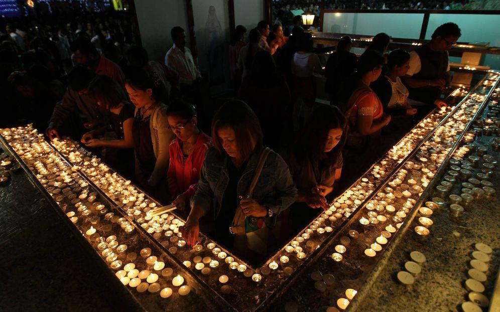 Foto: Cristianos encienden velas durante la misa de Navidad en la iglesia católica de Santa María, en Dubái. (EFE)