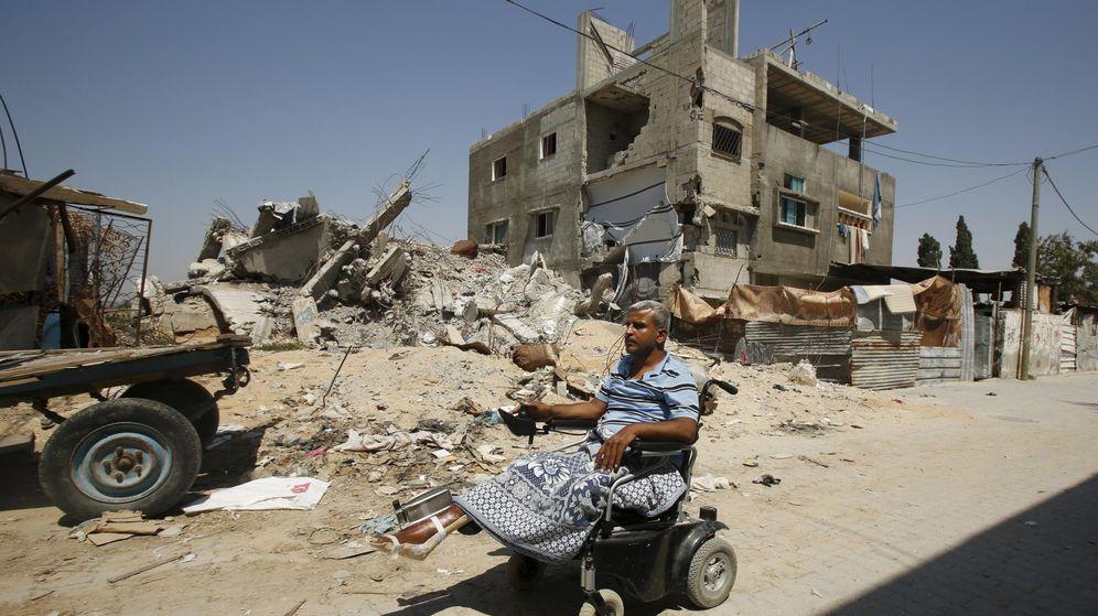 Foto: Un profesor palestino pasea en silla de ruedas frente a su casa en ruinas. (Reuters)