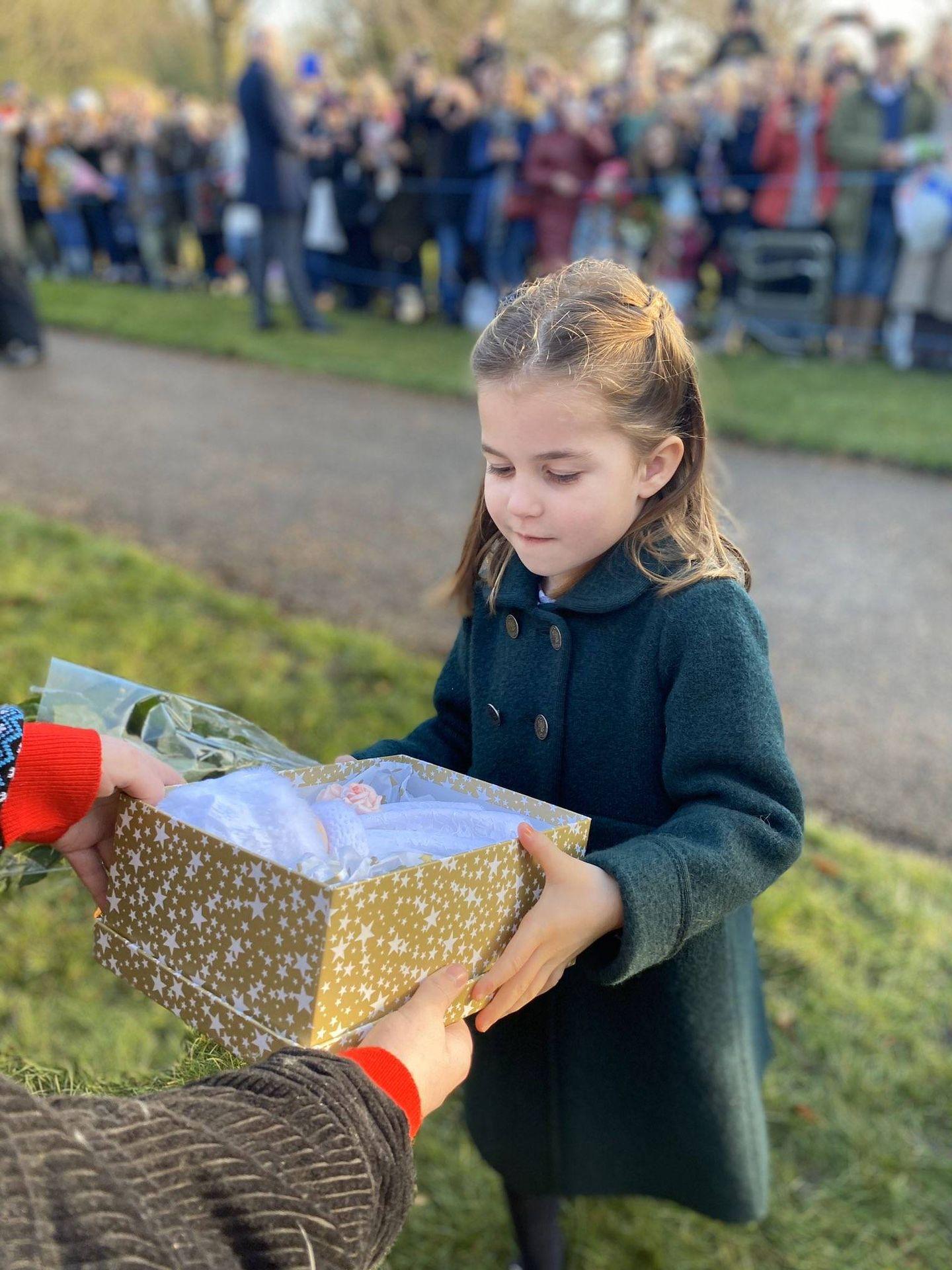 La princesa Charlotte, recibiendo uno de los regalos. (Twitter: @anvilius)
