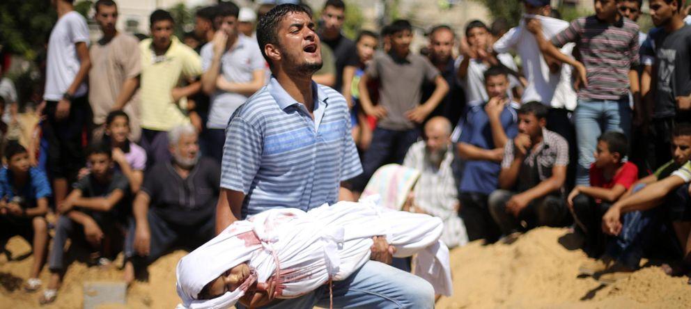 Foto: Un hombre palestino lleva en brazos el cuerpo de una niña fallecida durante los bombardeos en Gaza (Reuters)