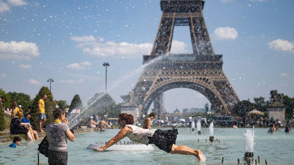 Foto: Ciudadanos se refrescan frente a la Torre Eiffel durante una ola de calor. (EFE)